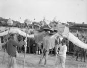 THE CHINESE LABOUR CORPS ON THE WESTERN FRONT, 1916-1918 (Q 8857) Chinese actors entertaining an audience of British and American soldiers, local inhabitants and Chinese workers at their camp at Samer, 26 May 1918. Two dragon processions ready for the fight. Copyright: © IWM. Original Source: http://www.iwm.org.uk/collections/item/object/205244662
